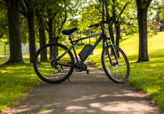 Electric bicycle in a park on a sunny day. Electric bicycle on a pathway in a park on a sunny day royalty free stock image