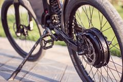 Electric bike motor wheel close up with pedal and rear shock absorber. Ebike bicycle environmentally friendly eco e-mountainbike transport. Healthy lifestyle Stock Image