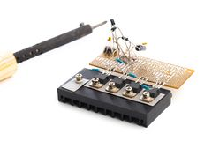 Electric board and a soldering iron isolated on a white background royalty free stock photography