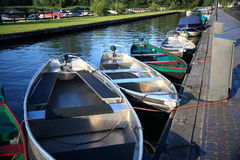 Electric boats docked in small canal. Small electric rental boats are docked in a small canal in, and connected to a charger stock photos