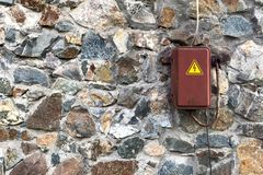 Electric box on natural stone wall.  Royalty Free Stock Image