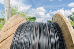 Electric cable roll black wire and blue sky. Background Stock Image