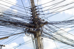 Electric cables tangle on electric pole Stock Photo