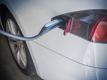 Electric Car Being Charged. Charging an electric car with the power supply plugged in Royalty Free Stock Photography