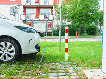 Electric car being charged at charging station. E-car being charged at charging station in public parking lot in Germany Royalty Free Stock Images