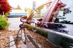 Electric Vehicle Being Charged in a Car Park. Electric Car being Charged at a Charging Station in a Parking Lot. Eco-friendly Means of Transport Concept royalty free stock images
