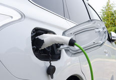 Electric Car Being Charged. Electric white Car Being Charged Royalty Free Stock Photography