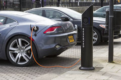 Electric car charge station in Milton Keynes, UK. MILTON KEYNES, ENGLAND - MARCH 5, 2015: Modern electric car charging at station dock point near parking lot Stock Photography