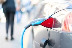 An electric car is charged with energy by a road dispenser.  royalty free stock images