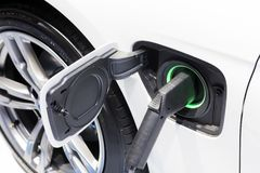 The electric car charger plugged in to the socket. The modern electric car charging the battery stock photos