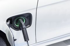 The electric car charger plugged in to the socket. Royalty Free Stock Photo