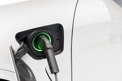 The electric car charger plugged in to the socket. Royalty Free Stock Photography