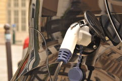 Electric car charging. Black electric car chargin from a streetside charger stock photo