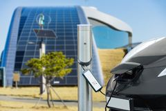 Electric car is charging near the station Stock Photos