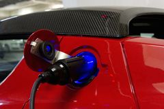 Electric car charging with plug Royalty Free Stock Photo