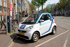 Electric car is charging at a point in the street Royalty Free Stock Images
