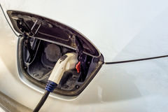 Electric car charging at recharging station. Close-up of the plug Royalty Free Stock Photography