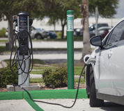 Electric car charging station. A plug-in electric car being re-charged at a charging station Stock Photography