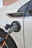 Electric Car Charging. A Volt electric charge plugged in to a power source to recharge Royalty Free Stock Photo