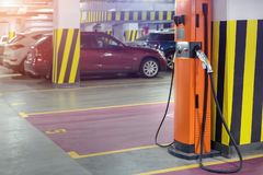 Electric car fast charging station at indoor underground parking. Power supply point network for hybrid electric car. Charging battery. Eco green energy royalty free stock photography