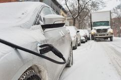 Electric car getting charged. In Montreal during snowstorm Stock Photos