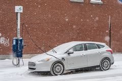 Electric car getting charged in Montreal during snowstorm. Montreal, Canada - 12 December 2017: Electric car getting charged in Montreal during snowstorm royalty free stock image