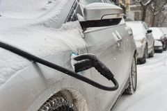 Electric car getting charged. In Montreal during snowstorm royalty free stock image