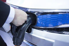 Electric car hand held at charge point Stock Photo