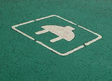 Electric car parking and charging sign. White plug painted on green background in the asphalt.  Stock Photography