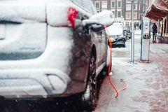 Electric car plug charging in the winter. Amsterdam, Netherlands stock images