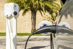 Electric car plugged by cable to charging station. With palm tree and old walls as background Royalty Free Stock Photos