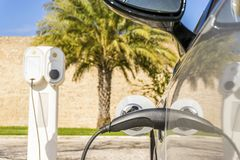 Electric car plugged by cable to charging station. With palm tree and old walls as background Royalty Free Stock Images