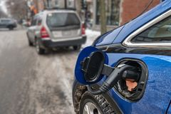 Electric car plugged in and charging in the wintertime Montreal, CA stock image