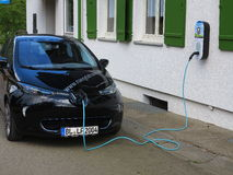 Electric car plugged Stock Photos