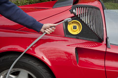 Electric car recharging. Red electric car home refueling with a 220 volt line Stock Photography