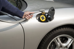 Electric car recharging. Silver electric car home refueling with a 220 volt line Royalty Free Stock Photo