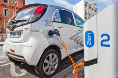 Electric car recharging at station. NICE, FRANCE - AUGUST 23, 2014: Electric car at Auto Bleue charging station - popular urban self service car sharing service Royalty Free Stock Image