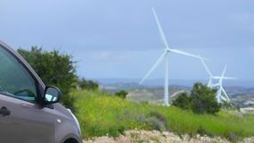 Electric car, wind turbines rotating, green energy source, clean environment. Stock footage stock footage