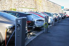Electric cars plugged and charging at a car park in Oslo Norway. Oslo, Norway - 2016-10-05 : Electric cars plugged in and charging at a car park on the street in royalty free stock image