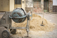 Electric cement Mixer, sand and a shovel for construction Stock Photography