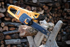 Electric chainsaw. On trestle and wood on background Stock Photo