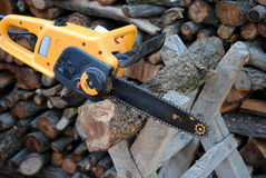 Electric chainsaw. On trestle and wood on background Stock Photos