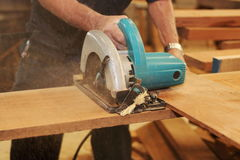 Electric circular saw is being cut a piece of wood against hands of senior carpenter in carpentry workshop. Stock Photos