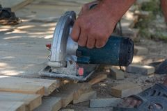 Electric circular saw is being cut a piece of wood by carpenter stock photo