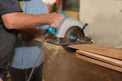 Electric circular saw is being sawed with a piece of wood by a senior carpenter in carpentry workshop. Royalty Free Stock Image