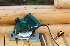 Electric circular saw and knife on a wooden platform Stock Photo