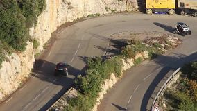Electric City Cars on a Hairpin Turn on the French Alps Road. La Turbie, France - November 4, 2015: Electric City Cars (White Renault Twizy and Black Smart stock video footage
