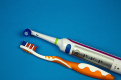 Electric and classical toothbrush isolated blue Royalty Free Stock Photography