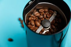 Electric coffee grinder with roasted coffee beans stock images