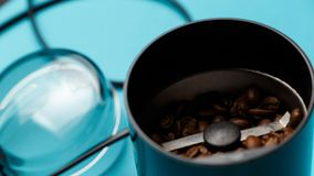 Electric coffee grinder with roasted coffee beans on the kitchen table with blue tabletop royalty free stock images